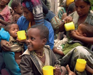 Smiling child and others drinking nutrients.