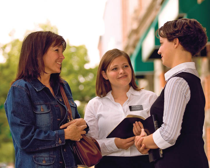 A photo of sister missionaries teaching a woman on the street.