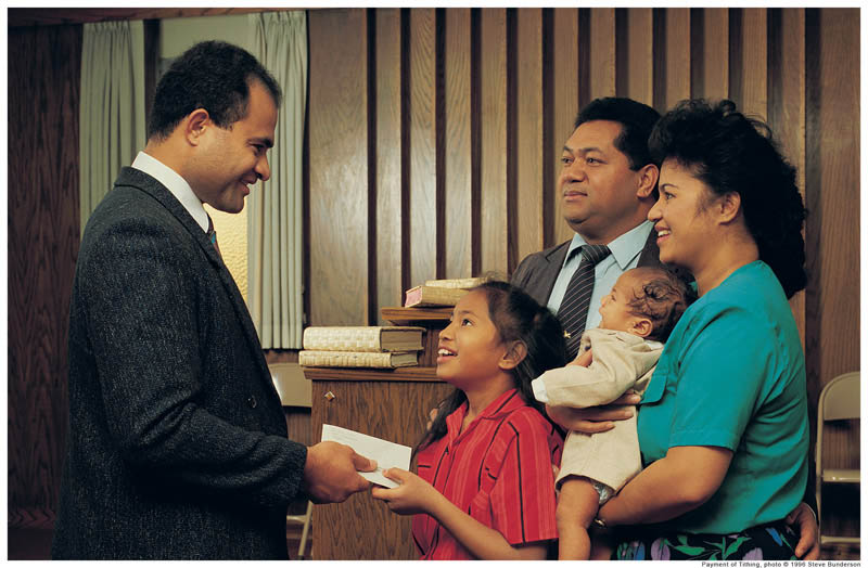 A photo of a family handing a tithing envelope to their bishop in church.