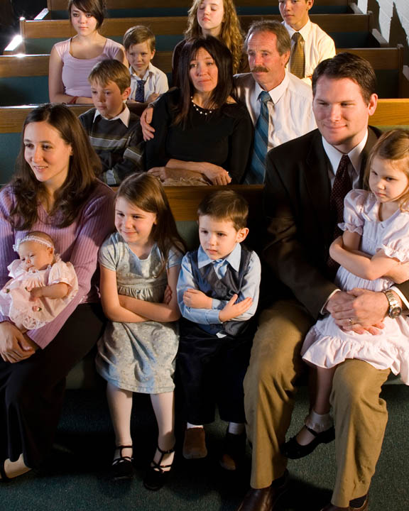 A photo of several Mormon families sitting in the pews of the chapel at a church.