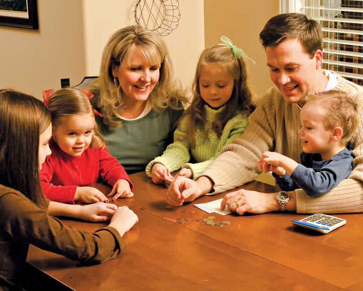 A photo of a young family gathered around a table to learn about paying tithing.
