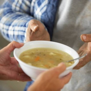 Handing a bowl of soup to someone in need.