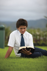 Young man reading the Book of Mormon