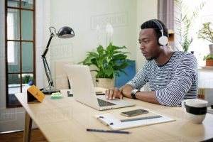 young man listening to music in home office